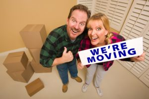 Goofy Thumbs Up Couple Holding We're Moving Sign in Room with Packed Cardboard Boxes.